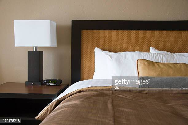 Lamp with white square shade and bed in brown and white