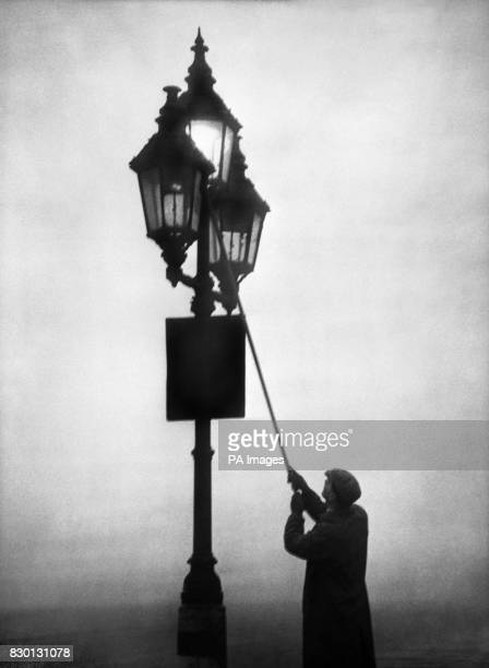 A lamplighter on his rounds on a foggy day at Blackfriars London