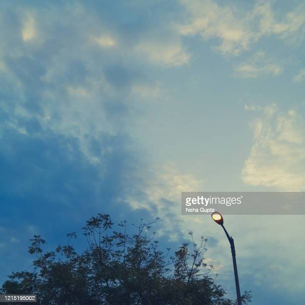lamppost against the cloudy sky - neha gupta stock pictures, royalty-free photos & images