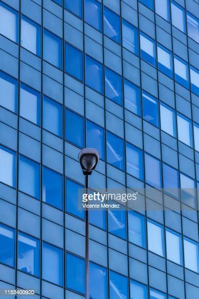 lamppost and glass building - vicente méndez fotografías e imágenes de stock