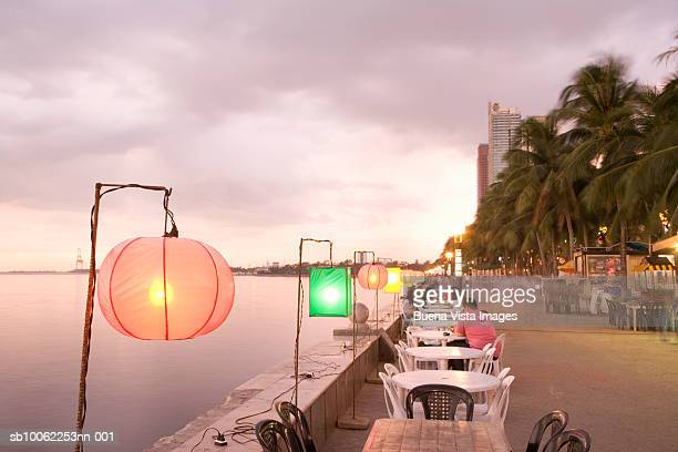 lamps at sunset in restaurant on waterfront over manila bay - manila bay stock photos and pictures