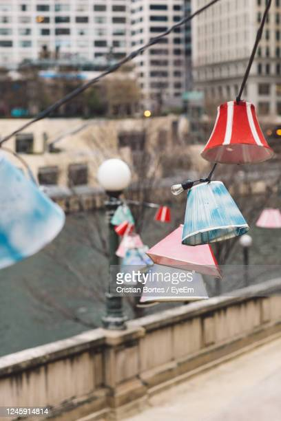 lamps hanging on street against buildings in city - bortes stock pictures, royalty-free photos & images