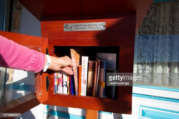lamy, nm: hand removing book from a little free library - free of charge stock pictures, royalty-free photos & images