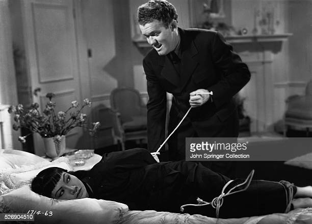 Lan Ying Lin is tied up by Otto Hartman when she is caught investigating his smuggling ring in the 1937 film Daughter of Shanghai