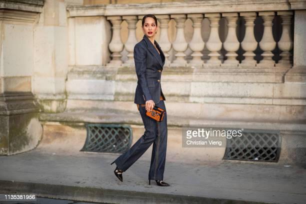Lana El Sahely is seen wearing dark denim jeans jacket and pants mini clutch outside Louis Vuitton during Paris Fashion Week Womenswear Fall/Winter...