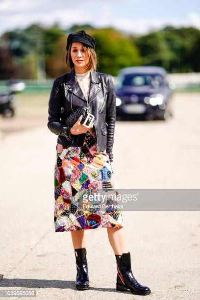 Lana El Sahely wears a cap hat a black leather jacket a multicolor dress outside Dior during Paris Fashion Week Womenswear Spring/Summer 2019 on...