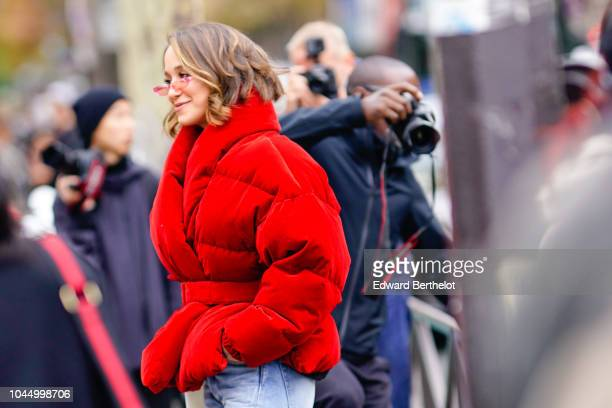 Lana El Sahely wears a red oversize puffer coat denim jeans pants sunglasses outside Miu Miu during Paris Fashion Week Womenswear Spring/Summer 2019...
