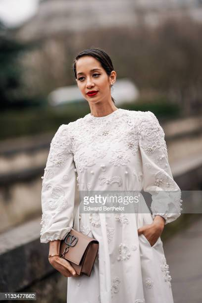 Lana El Sahely wears a white lace embroidered dress a Valentino bag heels shoes outside Valentino during Paris Fashion Week Womenswear Fall/Winter...