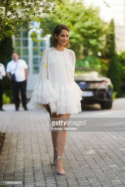 Lana El Sahely wears a white lace ruffled dress, outside Giambattista Valli, during Paris Fashion Week -Haute Couture Fall/Winter 2019/2020, on July...