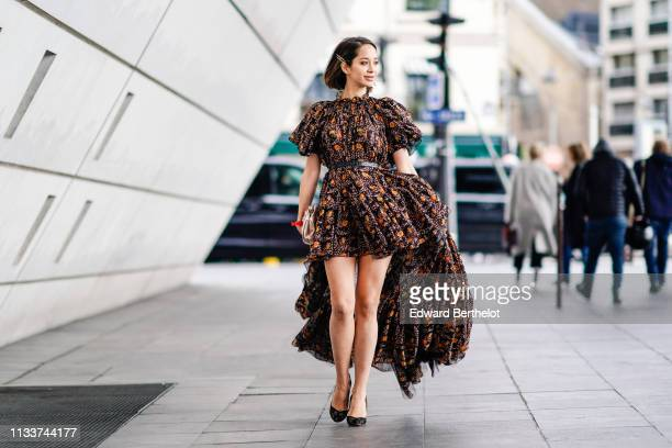 Lana El Sahely wears an orange and black floral print asymmetric gathered dress with puff sleeves black shoes a shiny beige clutch outside...