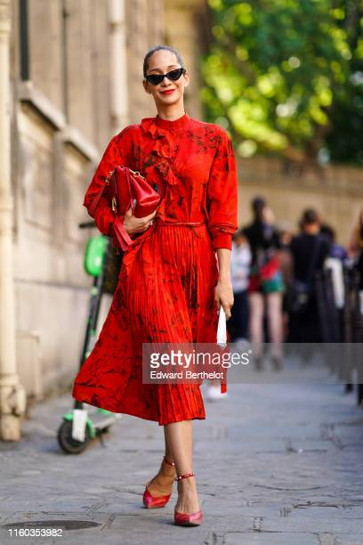 Lana El Sahely wears sunglasses a red floral print pleated dress a red bag red shoes outside Valentino during Paris Fashion Week Haute Couture...