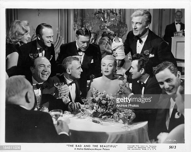 Lana Turner at table with Walter Pidgeon and Gilbert Roland beside her in a scene from the film 'The Bad And The Beautiful' 1952