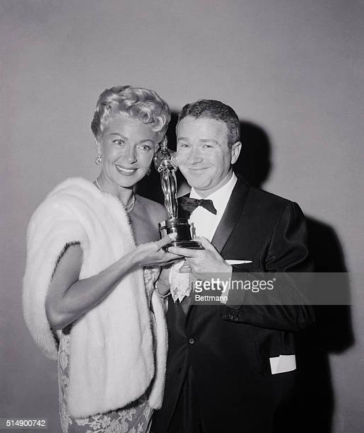 Lana Turner nominee for the best actress plants a kiss on the cheek of red buttons after presenting him his Oscar tonight at the 30th annual academy...