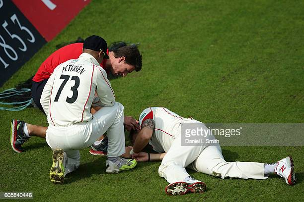 Lancashire Alviro Petersen attends to Kyle Jarvis after both collided during day four of the Specsavers County Championship Division One match...