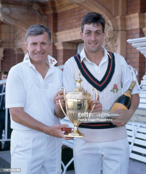 Lancashire captain David Hughes holds the tournament trophy with teammate and man of the match Mike Watkinson during the presentation ceremony after...