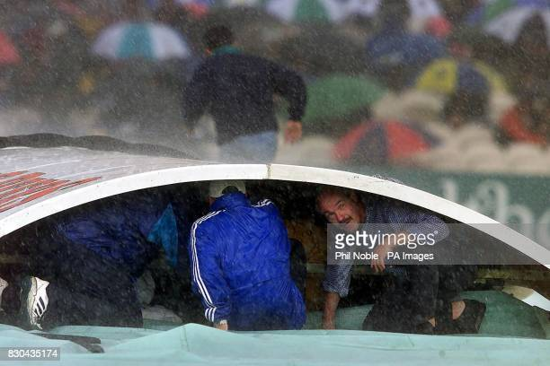Lancashire head groundsman Peter Marren shelters under the covers, after rain stopped play in the Third Test cricket match between England and West...