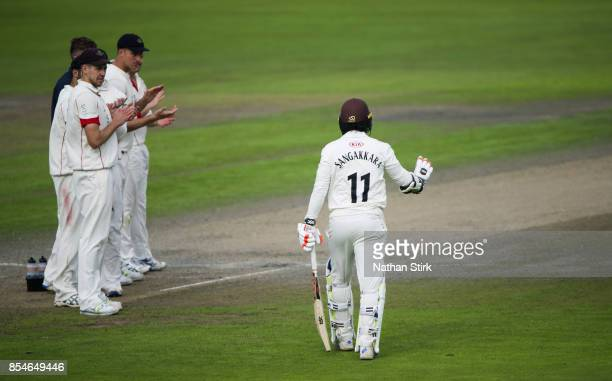 Lancashire players clap Kumar Sangakkara of Surrey as he walks onto the pitch for the last time during the County Championship Division One match...