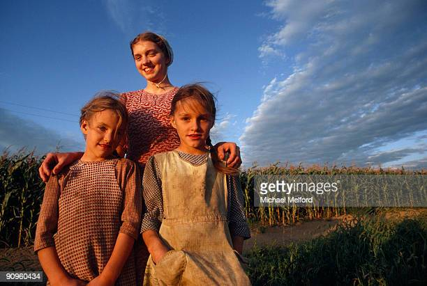 Amish Girls smiling near a corn field.