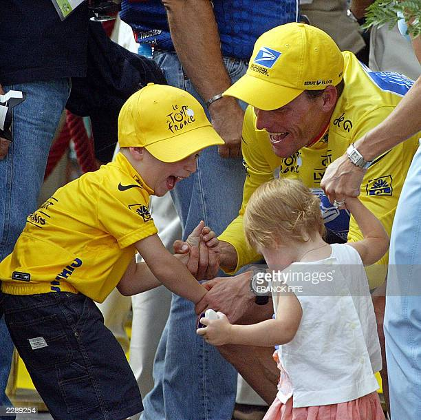 US Lance Armstrong celebrates his victory with his son Luke while one of his daughter's and his wife Kristin look on at the end of the 20th and last...