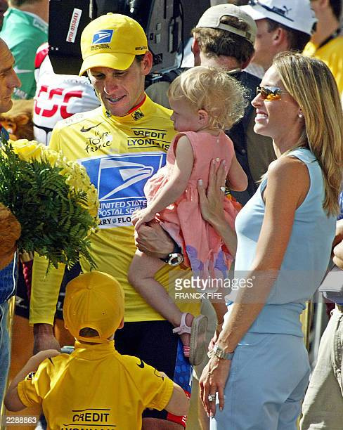 US Lance Armstrong celebrates his victory with one of his daughter's while his son Luke and wife Kristin look on at the end of the 20th and last...