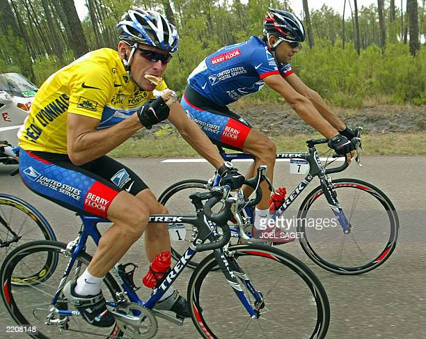 US Lance Armstrong eats as he rides with his teammate Czech Pavel Padrnos during the 17th stage of the 90th Tour de France between Dax and Bordeaux...