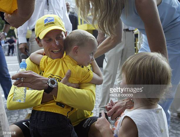 US Lance Armstrong gives a hug to his son Luke while his wife Kristin and daughter look on at the end of the 20th and last stage of the 90th Tour de...