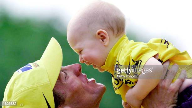 Lance Armstrong holds his 9 month old boy Luke on the victory podium after cruising to his second Tour de France championship July 23 2000 in Paris...
