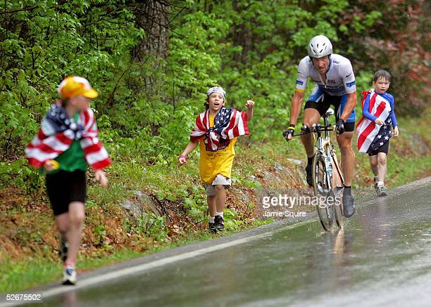Lance Armstrong of the Discovery Channel Pro Cycling Team climbs a hill as children cheer during the individual time trial, stage three, of the Tour...