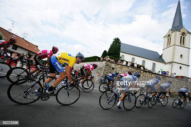 Lance Armstrong of the USA in the yellow jersey riding for the Discovery Channel cycling team rides by a church in a french village during stage 9 of...