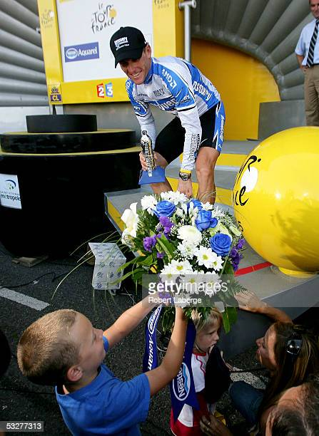 Lance Armstrong of the USA riding for the Discovery Channel cycling team gives flowers to his children Luke Grace and Isabella as girlfriend Sheryl...