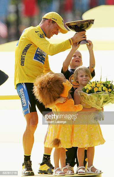 Lance Armstrong of the USA riding for the Discovery Channel cycling team celebrates on the podium with his children Luke Isabella and Grace after...