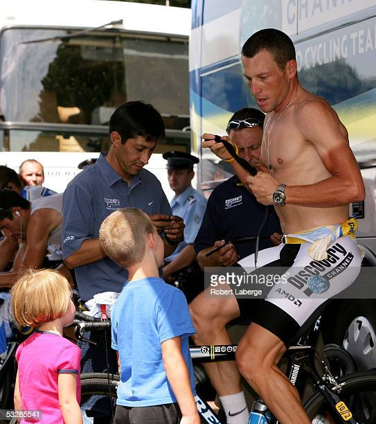 Lance Armstrong of the USA riding for the Discovery Channel cycling team changes his heart rate monitor as his children look on before the start of...
