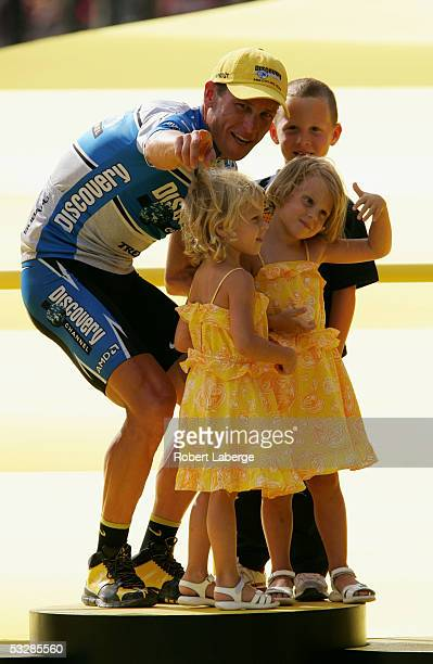 Lance Armstrong of the USA riding for the Discovery Channel cycling team with his children Luke Grace and Isabella on the podium after stage 21 of...