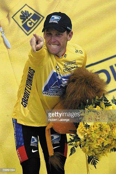 Lance Armstrong of the USA riding for the US Postal-Berry Floor team points at one of his teammates as he stands on the podium after winning stage...
