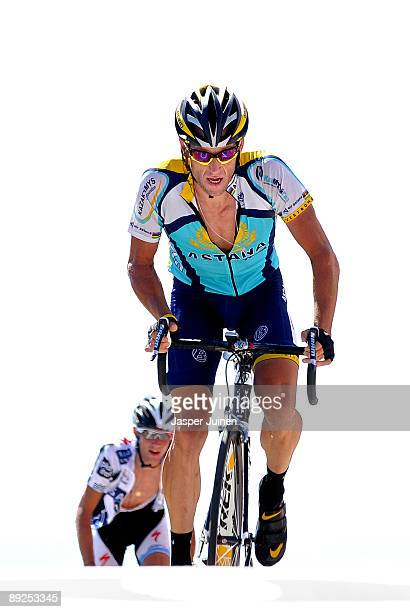 Lance Armstrong of USA and team Astana crosses the finishline backdropped by Frank Schleck of Luxembourg and team Saxo Bank at the end of stage 20...