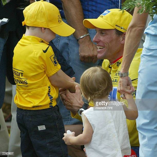 US Lance Armstrong talks with his son Luke while one of his daughter's and wife Kristin look on at the end of the 20th and last stage of the 90th...