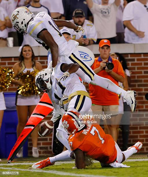 Lance Austin of the Georgia Tech Yellow Jackets fumbles an interception into the end zone as he is hit by teammate Corey Griffin and Mike Williams of...