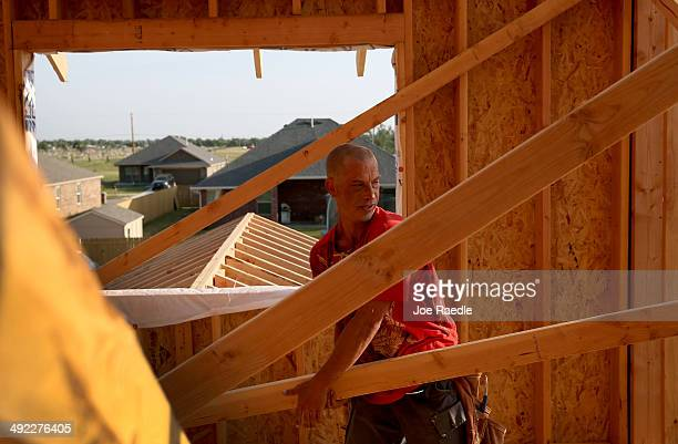 Lance Barnett works on building a new home to replace the one that was destroyed almost one year ago by a tornado on May 19 2014 in Moore Oklahoma...