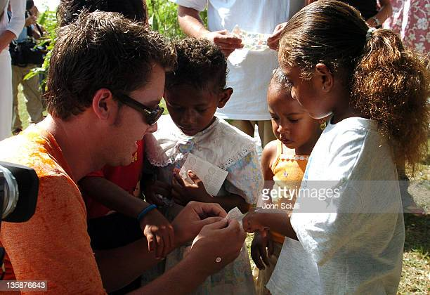 Lance Bass hands out stickers to village children during Kelly Slater Invitational Fiji Day 2 Mome Village Tour in Mome Village Tavarua Island Fiji