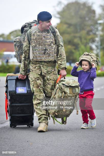 Lance Bombardier Scott Campbell makes his way to the car with his kit helped by his son Taylor aged four as Soldiers from 19th Regiment Royal...