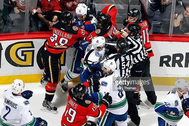 Lance Bouma Deryk Engelland and teammates of the Calgary Flames get into a postwhistle scrum with Jannik Hansen Daniel Sedin and teammates of the...