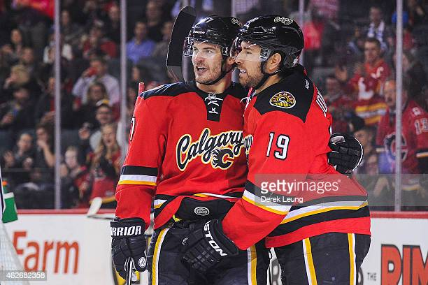 Lance Bouma of the Calgary Flames congratulates teammate David Jones on his goal in the first period against the Winnipeg Jets during an NHL game at...