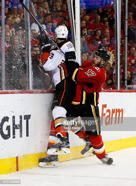 Lance Bouma of the Calgary Flames hits Clayton Stoner of the Anaheim Ducks against the boards in Game Four of the Western Conference Semifinals...