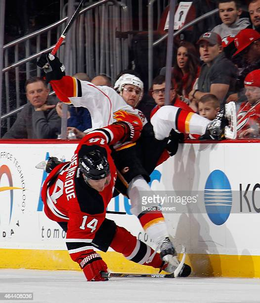 Lance Bouma of the Calgary Flames is hit by Adam Henrique of the New Jersey Devils during the first period at the Prudential Center on February 25...