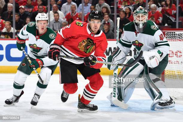Lance Bouma of the Chicago Blackhawks and Gustav Olofsson of the Minnesota Wild watch for the puck next to goalie Devan Dubnyk in the first period at...