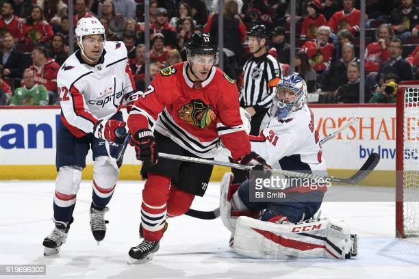 Lance Bouma of the Chicago Blackhawks and Madison Bowey of the Washington Capitals skate in front of goalie Philipp Grubauer in the third period at...
