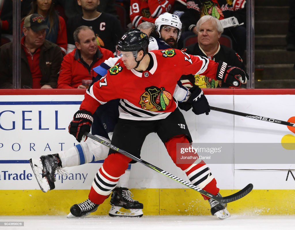 Lance Bouma #17 of the Chicago Blackhawks pins Mathieu Perreault #85 of the Winnipeg Jets against the boards at the United Center on January 12, 2018 in Chicago, Illinois. The Blackhawks defeated the Jets 2-1.