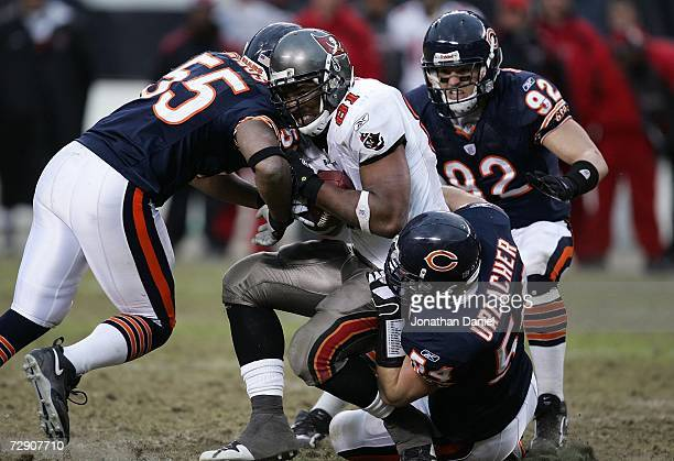 Lance Briggs Brian Urlacher and Hunter Hillenmeyer of the Chicago Bears tackle Alex Smith of the Tampa Bay Buccaneers December 17 2006 at Soldier...