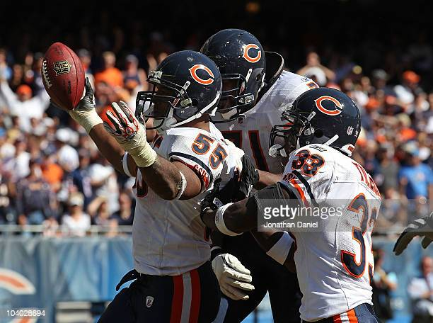 Lance Briggs of the Chicago Bears celebrates a turnover with teammates Israel Idonije and Charles Tillman during the NFL season opening game against...