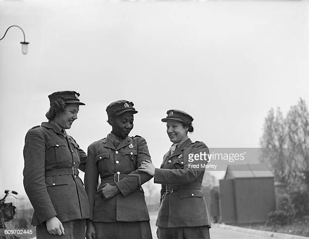 Lance Corporal Adina Williams of the British Auxiliary Territorial Service is congratulated by members of her unit after receiving her first stripe...